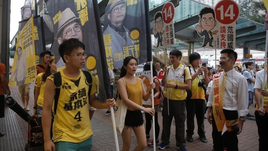 Radical activist candidate Gary Fan, right, looks at the supporters of Horace Chin, a radical activist candidate, during their election campaign in Hong Kong Saturday, Sept. 3, 2016. Hong Kongers are heading to the polls Sunday in the first major election since 2014 pro-democracy street protests. A new crop of radical activists are challenging both pro-Beijing rivals and Hong Kong's mainstream pro-democracy parties for seats in the Legislative Council. A series of vandalized posters are a sign that the elections are the most contentious since the 1997 British handover of the city to China. At left is Hong Kong localist leader Edward Leung Tin-kei, one of the candidates rejected to participate in the Legislative Council elections. (AP Photo/Kin Cheung)