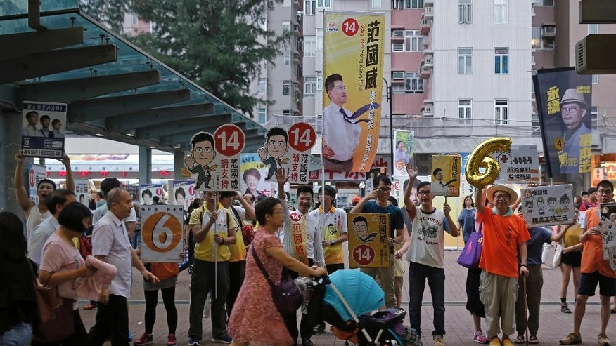 Supporters from different political groups line to urge people to vote,  at the upcoming Legislative Council elections in Hong Kong Saturday, Sept. 3, 2016. Hong Kongers are heading to the polls Sunday in the first major election since 2014 pro-democracy street protests. A new crop of radical activists are challenging both pro-Beijing rivals and Hong Kong's mainstream pro-democracy parties for seats in the Legislative Council. A series of vandalized posters are a sign that the elections are the most contentious since the 1997 British handover of the city to China. At left is Hong Kong localist leader Edward Leung Tin-kei, one of the candidates rejected to participate in the Legislative Council elections. (AP Photo/Kin Cheung)