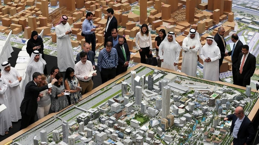 "Journalists and Emirati officials listen to Morgan Parker, Chief Operating Officer of Dubai Holding, 1st left front row, as he explains over the architectural model of the ""Jumeriah Central"" development, a U.S. $ 20 billion project, during a press briefing in Dubai, United Arab Emirates, Sunday, Sept. 4, 2016. The company controlled by Dubai's ruler has unveiled plans for a vast mixed-use development that will create thousands of new homes and hotel rooms. (AP Photo/Kamran Jebreili)"
