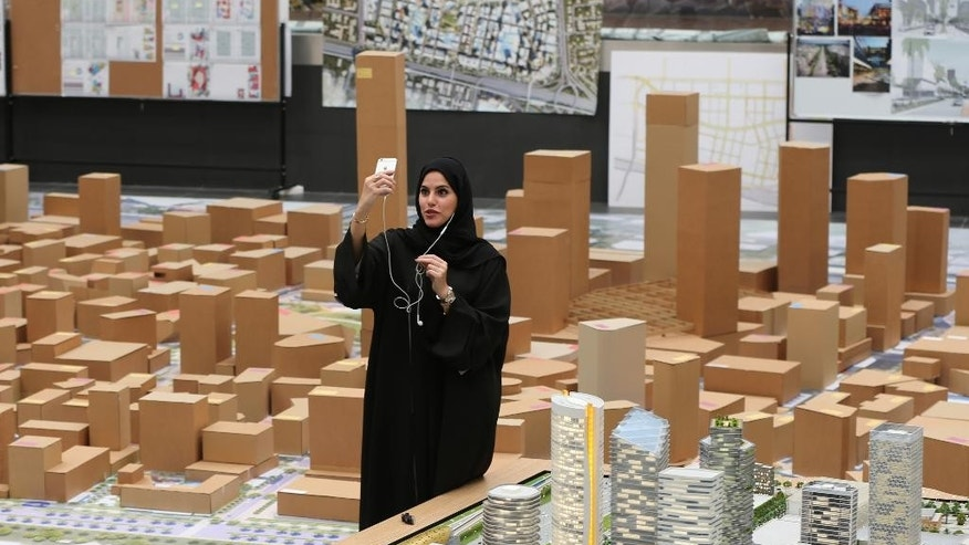 "An Emirati films herself on a mobile phone next to an architectural model of the ""Jumeriah Central"" development, a U.S. $ 20 billion project, during a press briefing in Dubai, United Arab Emirates, Sunday, Sept. 4, 2016. The company controlled by Dubai's ruler has unveiled plans for a vast mixed-use development that will create thousands of new homes and hotel rooms. (AP Photo/Kamran Jebreili)"