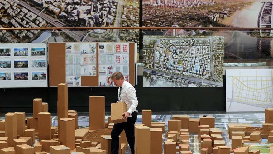 "An employee of Dubai Holding moves one of the cardboard building blocks in an architectural model of the ""Jumeriah Central"" development, a U.S. $ 20 billion project, during a press briefing in Dubai, United Arab Emirates, Sunday, Sept. 4, 2016. The company controlled by Dubai's ruler has unveiled plans for a vast mixed-use development that will create thousands of new homes and hotel rooms. (AP Photo/Kamran Jebreili)"