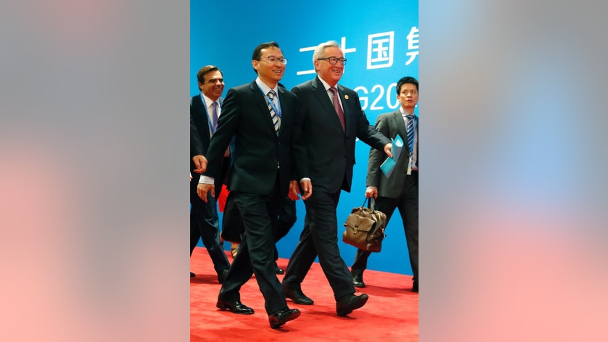 European Commission President Jean-Claude Juncker, second from right, is escorted by Chinese official as he arrives at the G20 Summit in Hangzhou in eastern China's Zhejiang province, Sunday, Sept. 4, 2016. European Union leaders have called for China to take action on its bloated steel industry and defended an order to Ireland to collect back taxes from Apple, highlighting the trade strains looming over a global economic summit. (AP Photo/Ng Han Guan)