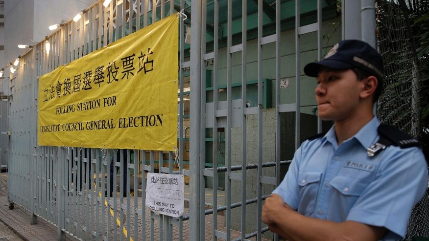 A police officer stands outside a polling station for the legislative council election Sunday, Sept. 4, 2016. Polls opened in Hong Kong Sunday for the specially administered Chinese city's most crucial election since the handover from Britain in 1997. The vote for lawmakers in the Legislative Council is also the first since 2014 pro-democracy street protests rocked the Asian financial hub. (AP Photo/Vincent Yu)