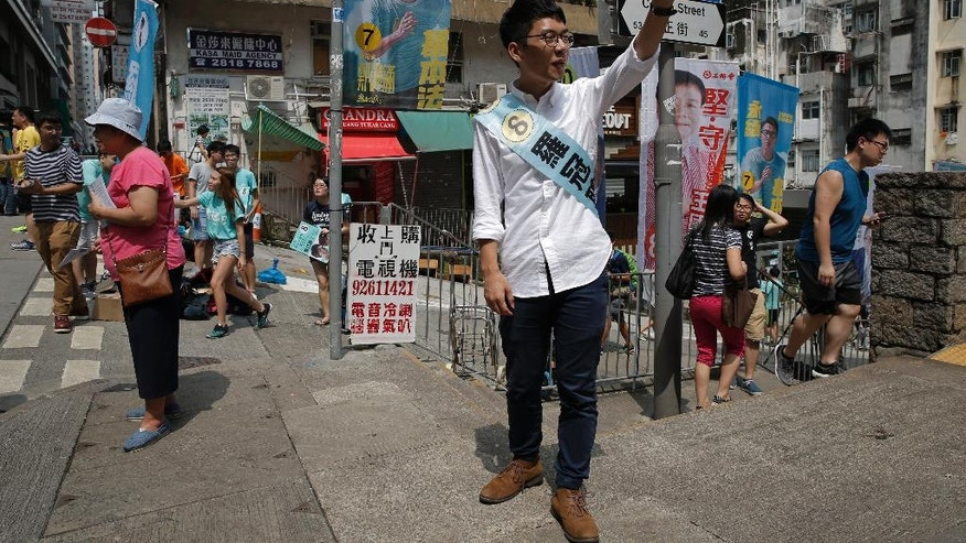 Hong Kong election candidate Nathan Law of the new political party Demosisto waves in Hong Kong, Sunday, Sept. 4, 2016. Polls opened in Hong Kong Sunday for the specially administered Chinese city's most crucial election since the handover from Britain in 1997. The vote for lawmakers in the Legislative Council is also the first since 2014 pro-democracy street protests rocked the Asian financial hub. (AP Photo/Kin Cheung)