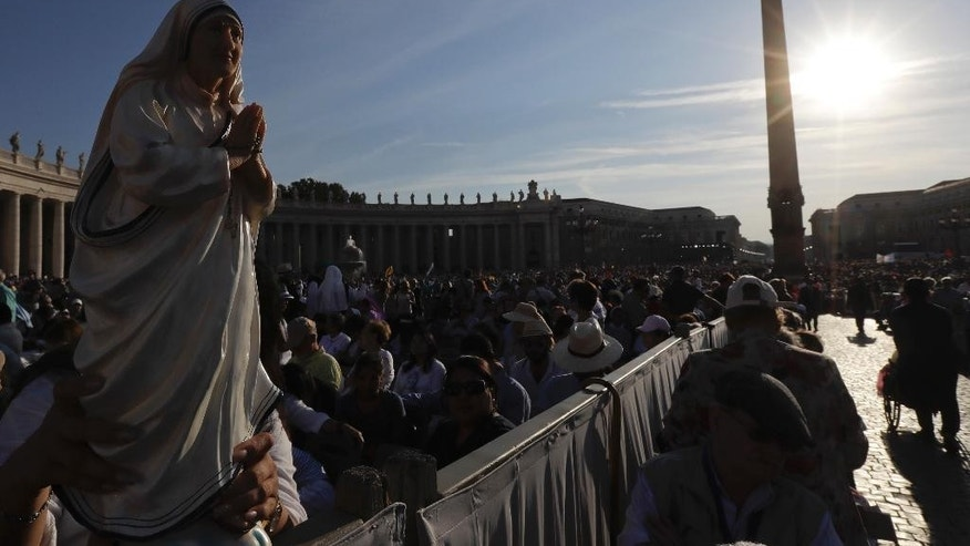Irma Escuero, of New York, holds a statue of Mother Teresa prior to the start of a mass celebrated by Pope Francis where will be canonized in St. Peter's Square, at the Vatican, Sunday, Sept. 4, 2016. Thousands of pilgrims thronged to St. Peter's Square on Sunday for the canonization of Mother Teresa, the tiny nun who cared for the world's most unwanted and became the icon of a Catholic Church that goes to the peripheries to tend to lost, wounded souls. (AP Photo/Gregorio Borgia)