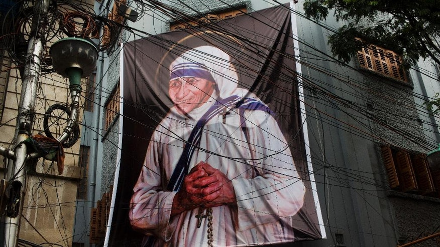 A giant picture of Mother Teresa is displayed outside the Missionaries of Charity Mother house in Kolkata, India, Saturday, Sept. 3, 2016. For many of the poor and destitute whom Mother Teresa served, the tiny nun was a living saint. Many at the Vatican would agree, but the Catholic Church nevertheless has a grueling process to make it official, involving volumes of historical research, the hunt for miracles and teams of experts to weigh the evidence. In Mother Teresa's case, the process will come to a formal end Sunday when Pope Francis declares the church's newest saint. (AP Photo/Bernat Armangue)