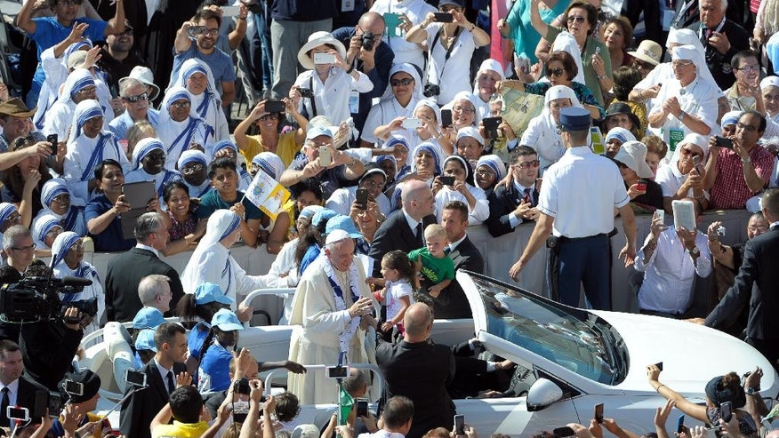 Pope Francis is driven through the crowd in St. Peter's Square at the Vatican during a jubilee audience for workers and volunteers of mercy, Saturday, Sept. 3, 2016. The square hosts a ceremony Sunday expected to draw hundreds of thousands of admirers of Mother Teresa, a nun who before her death in 1997, cared for the destitute who were dying in the streets of India. (L'Osservatore Romano/Pool Photo via AP)