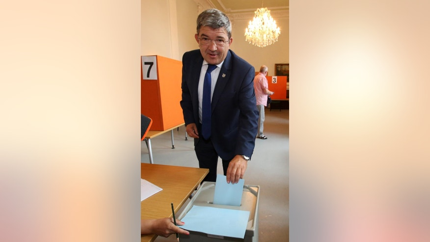 Top candidate  of chancellor Angela Merkel's Christian Democrats for the state elections in Mecklenburg-Western Pomerania, Lorenz Caffier, casts his vote in Neustrelitz, eastern Germany, Sunday Sept. 4, 2016. A nationalist, anti-immigration party looks set to perform strongly Sunday in  state election in the eastern German region where Chancellor Angela Merkel has her political base.   Polls ahead of the election in Mecklenburg-Western Pomerania show support for the three-year-old Alternative for Germany, or AfD, party running at over 20 percent.  (Bernd Wuestneck/dpa via AP)