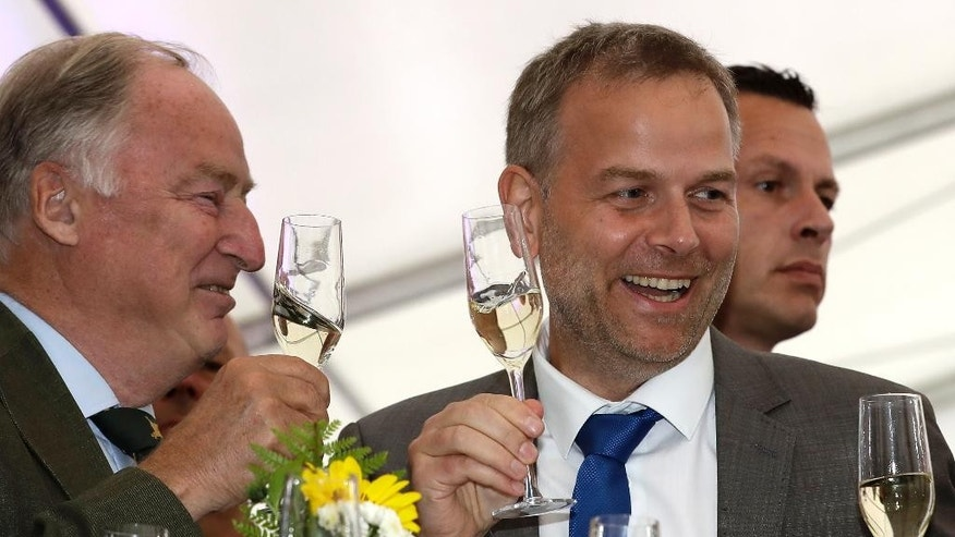 AfD member Alexander Gauland, left, and Leif-Erik Holm, top candidate of the AfD, toast at the gathering of the AfD (Alternative for Germany) party in Schwerin, Germany, Sunday, Sept. 4, 2016 after the  state elections in the German federal state of Mecklenburg-Western Pomerania.  Exit polls indicate that the nationalist, anti-immigration party has performed strongly in a state election in the region where Chancellor Angela Merkel has her political base, likely overtaking her conservative party.  ( AP Photo/Michael Sohn)