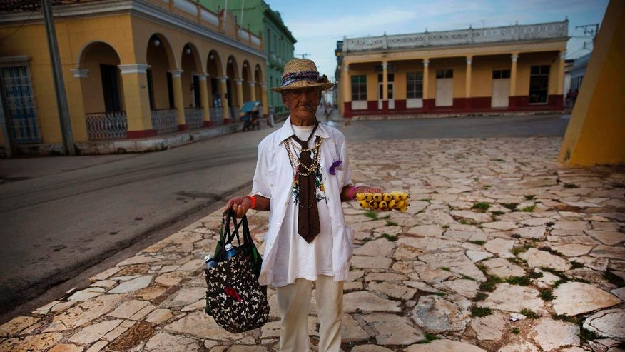 In this Sept. 1, 2016 photo, 90-year-old street vendor Antonio Bauza waits for tourists to sell bananas to, next to the village church in Remedios, Cuba. With the arrival of the first commercial flights from the U.S. to Cuba in more than 50 years, the Cuban government is welcoming the wave of new visitors and struggling to update infrastructure that's already overwhelmed. (AP Photo/Ramon Espinosa)