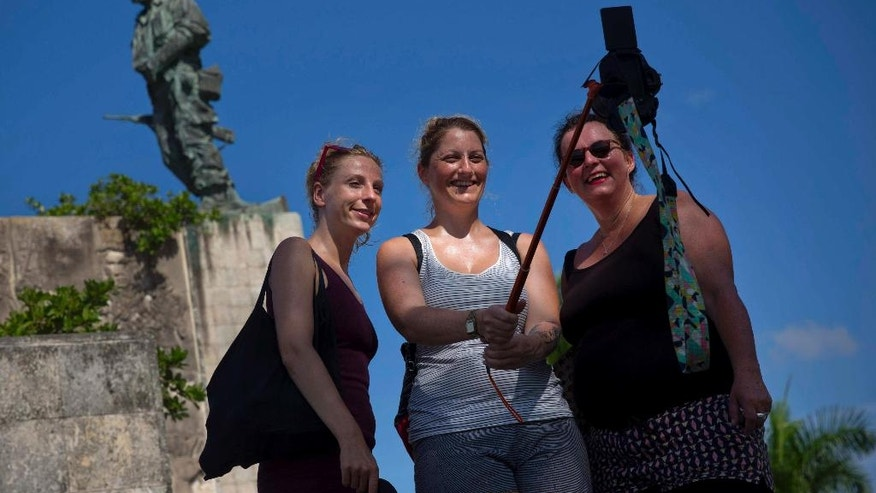 "In this Sept. 2, 2016 photo, tourists takes a selfie by the statue of revolutionary hero Ernesto ""Che"" Guevara in Santa Clara, Cuba. For travelers without relatives in Cuba it is about $200 each to fly from Fort Lauderdale to Santa Clara. (AP Photo/Ramon Espinosa)"