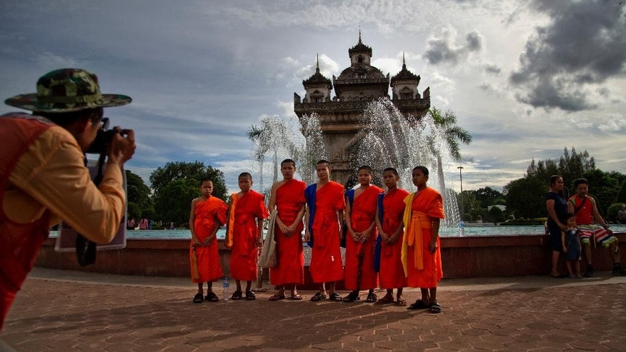 Buddhist monks pose for pictures standing in front of Patuxary Victory Gate in Vientiane, Laos, Sunday, Sep 4, 2016. The coming week will see a series of meetings of the member countries of the Association of Southeast Asian Nations (ASEAN) and their key dialogue partners scheduled to begin in Vientiane on September 6, 2016 .(AP Photo/ Gemunu Amarasinghe)