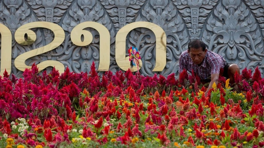 A worker adjusts flower pots decorating the entrance of a conference hall, the venue for meetings of the member countries of the Association of Southeast Asian Nations (ASEAN) and their key dialogue partners in Vientiane, Laos, Sunday, Sep 4, 2016. The coming week will see a series of meetings of the member countries ASEAN and their key dialogue partners scheduled to begin in Vientiane on September 6, 2016.(AP Photo/ Gemunu Amarasinghe)