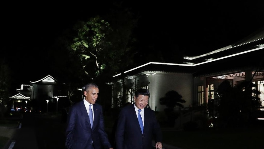"FILE - In this Sept. 3, 2016, file photo, U.S. President Barack Obama, left, and Chinese President Xi Jinping, walk together at West Lake State Guest House in Hangzhou in eastern China's Zhejiang province. Obama said ahead of his meeting with Xi that the U.S. has been ""very firm"" in response to Chinese military assertiveness. Xi told Obama that China will continue to ""unswervingly safeguard"" its territorial sovereignty and maritime rights and interests in the South China Sea, according to state-run Xinhua News Agency. (AP Photo/Carolyn Kaster, Pool, File)"
