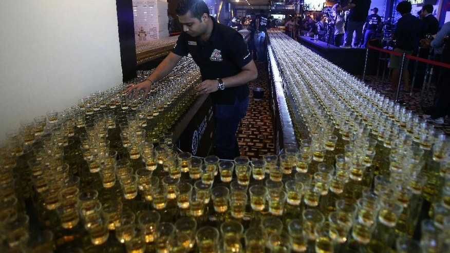 One of the crew members fixes new drinks after a misfire due to sound vibration before an attempt to make the world's longest domino drop shot on Monday, Sept. 5, 2016. The Citymax hotel's Huddle Sports Bar & Grille in Bur, Dubai attempts to break the world record with over 6,000 glasses of energy drink and shots of whiskey under the supervision of an observer from the Guinness Book of World Records. (AP Photo/Kamran Jebreili)