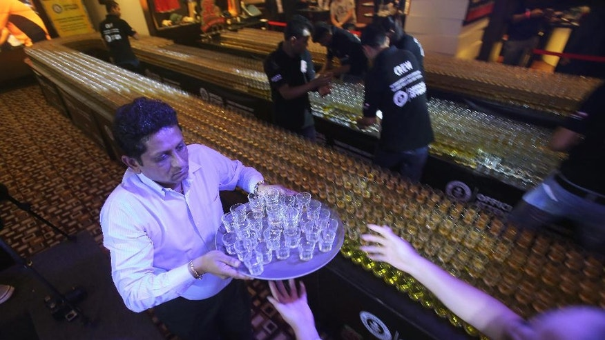 Managers and crew members fix new drinks after a misfire due to sound vibration before an attempt to make the world's longest domino drop shot on Monday, Sept. 5, 2016. The Citymax hotel's Huddle Sports Bar & Grille in Bur, Dubai attempts to break the world record with over 6,000 glasses of energy drink and shots of whiskey under the supervision of an observer from the Guinness Book of World Records. (AP Photo/Kamran Jebreili)