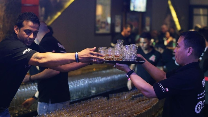 Crew members fixe new drinks after a misfire due to sound vibration before an attempt to make the world's longest domino drop shot on Monday, Sept. 5, 2016. The Citymax hotel's Huddle Sports Bar & Grille in Bur, Dubai attempts to break the world record with over 6,000 glasses of energy drink and shots of whiskey under the supervision of an observer from the Guinness Book of World Records. (AP Photo/Kamran Jebreili)