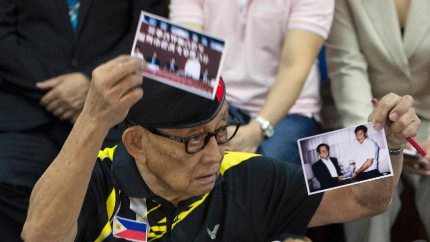 FILE -  In this Aug. 9, 2016, file photo, former Philippine President Fidel Ramos holds up what he says are photos of Chinese President Xi Jinping when he visited the Philippines in his youth during a press briefing at the Philippines consular office in Hong Kong. China has opposed raising its maritime disputes with neighbors at international meetings, two of which are taking place on Sunday, Sept. 4, 2016. To Beijing's pleasure, Philippine President Rodrigo Duterte said he will not raise the subject of China's compliance with an international tribunal's ruling that invalidated Beijing's territorial claims in the South China Sea. Preferring a quiet diplomacy, Duterte in August sent his special envoy Ramos to meet with Chinese officials and they agreed on the need to reduce tensions through talks. (AP Photo/Ng Han Guan, File)