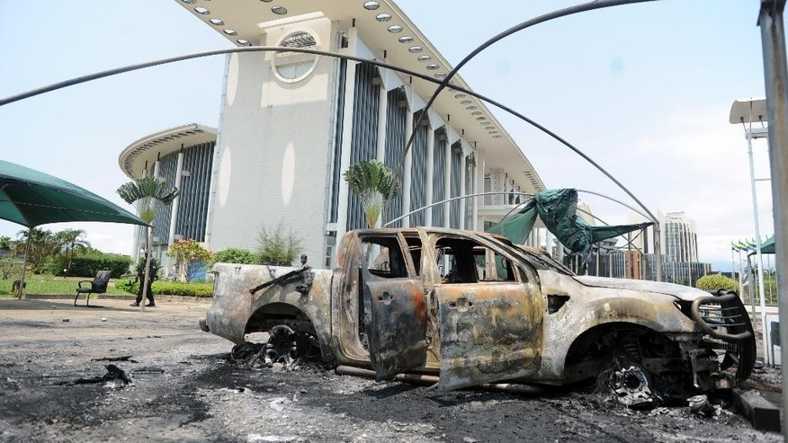 A burned vehicle sits outside a government building after an election protest in Libreville, Gabon, Thursday Sept. 1, 2016. Gabon's newly re-elected president sought to assert authority Thursday as the presidential guard attacked the opposition candidate's party headquarters overnight, killing at least one person and injuring more than a dozen amid fiery protests that have seen hundreds detained and the internet blocked. (AP Photo/Joel Bouopda)
