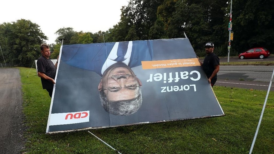 Workers remove an election poster of German Chancellor Angela Merkel's CDU top candidate Lorenz Caffier for the election in Mecklenburg-Western Pomerania, Monday, Sept. 5, 2016. The nationalist, anti-immigration party Alternative for Germnany, AfD, has performed strongly in the state election Sunday in the region where Merkel has her political base, overtaking her conservatives to take second place amid discontent with her migrant policies. (Christian Charisius/dpa via AP)