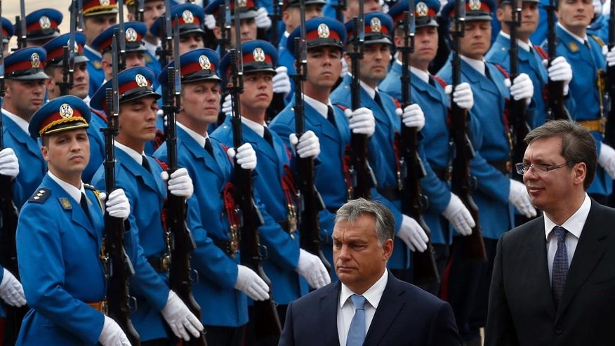 Hungary's Prime Minister Viktor Orban, center, reviews the honor guard upon his arrival at the Serbia Palace to meet Serbian Prime Minister Aleksandar Vucic, right, in Belgrade, Serbia, Monday, Sept. 5, 2016. Orban arrived on a one-day visit to Serbia. (AP Photo/Darko Vojinovic)