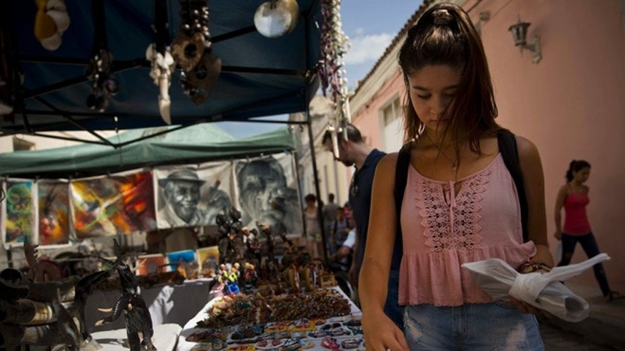 "In this Sept. 1, 2016 photo, tourist Sophia Compton from Chicago looks for souvenirs at a market in Santa Clara, Cuba. ""The best tourist there is, is the American tourist,"" said 25-year-old Liban Bermudez as he sold Compton a pair of handmade leather sandals from his stand off Santa Clara's main plaza. ""They're the ones that buy the most."" (AP Photo/Ramon Espinosa)"