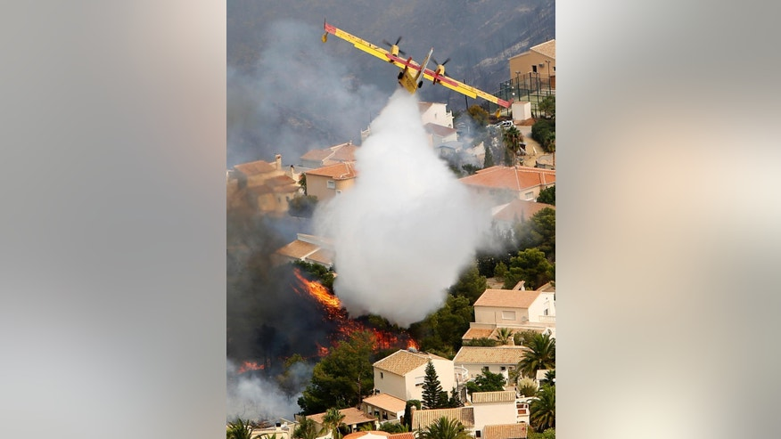 A plane works to extinguish a wildfire  as it burns nearby Benitachel village, eastern Spain, Monday, Sept. 5, 2016. Spanish firefighters are still working to bring under control a forest blaze near Valencia that forced the evacuation of around 1,000 people. Authorities said more than 200 firefighters with 65 vehicles were deployed Monday to the wildfire some 350 kilometers (220 miles) southeast of Madrid. (AP Photo/Alberto Saiz)