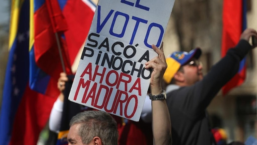 "A Venezuelan living in Chile holds up a sign that reads in Spanish ""The vote ousted Pinocho,"" referring to Chile's late dictator Gen. Augusto Pinochet, ""Now Maduro,"" during a protest against the government of Venezuela's President Nicolas Maduro in Santiago, Chile, Saturday, Sept. 3, 2016. Protesters joined their countrymen in Venezuela who have coined recent protests as ""taking of Caracas"" to pressure electoral authorities to allow a recall referendum against Maduro this year. (AP Photo/Esteban Felix)"