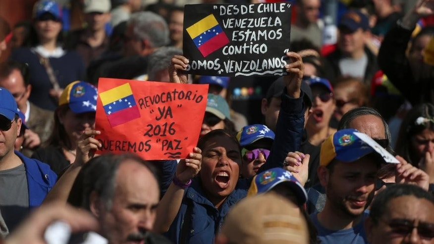 "Venezuelans living in Chile protest the government of Venezuela's President Nicolas Maduro in Santiago, Chile, Saturday, Sept. 3, 2016. Protesters joined demonstrators in Caracas who have coined recent protests as the ""Taking of Caracas"" to pressure electoral authorities to allow a recall referendum against Maduro this year. The signs read in Spanish: ""Recall now. 2016. We want peace,"" left, and ""From Chile we are with you Venezuela. We're Venezuelans."" (AP Photo/Esteban Felix)"
