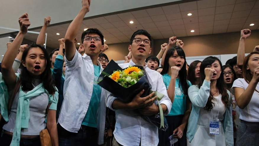 Nathan Law, center, of the political party Demosisto, who helped lead the 2014 protests, celebrates with teen protest leader Joshua Wong, second from left, and his supporters after winning a seat at the legislative council elections in Hong Kong, Monday, Sept. 5, 2016. A new wave of anti-China activists appeared headed for victory in Hong Kong's most pivotal elections since the handover from Britain in 1997, which could set the stage for a fresh round of political confrontations over Beijing's control of the city. (AP Photo/Vincent Yu)