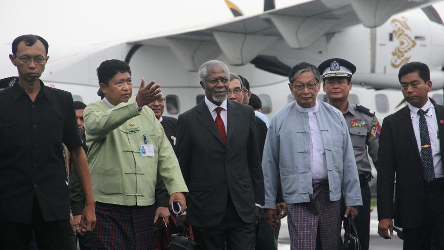 Former United Nations Secretary-General Kofi Annan, who chairs the recently created Rakhine State Advisory Commission, is escorted by local authorities as he arrvies arrives at the airport in Sittwe, Rakhine state, Myanmar. More than 1,000 Buddhists in Sittwe wracked by religious and ethnic strife protested Tuesday's arrival of Annan, saying the Ghanaian is meddling in the country's affairs by leading a government-appointed commission to find solutions to the conflict. (AP Photo/Esther Htusan)