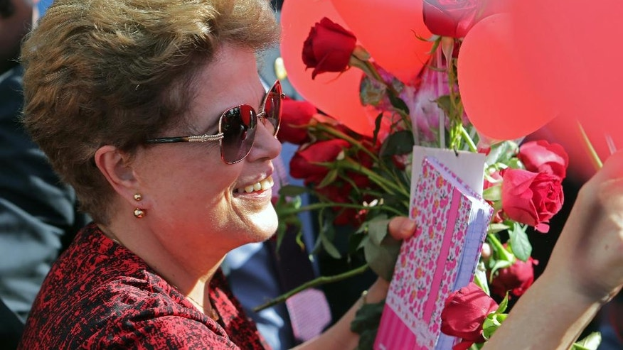 Brazil's former President Dilma Rousseff, who was impeached, receives flowers and gifts from supporters as she leaves the presidential residence, Alvorada Palace, in Brasilia, Brazil, Tuesday, Sept. 6, 2016. Rousseff, who has vowed to form a strong opposition against interim President Michel Temer, who was once her vice president, is appealing her impeachment to the Supreme Court. Legal experts say her appeal is unlikely to succeed as several appeals during the months-long impeachment process were rejected. (AP Photo/Eraldo Peres)