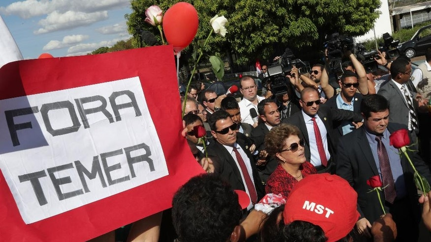 "Brazil's impeached President Dilma Rousseff, center right in red shirt, walks past a sign held by a supporter that reads in Portuguese: ""Get out Temer"" as she leaves the official presidential residence, Alvorada Palace, in Brasilia, Brazil, Tuesday, Sept. 6, 2016. Rousseff, who has vowed to form a strong opposition against interim President Michel Temer, who was once her vice president, is appealing her impeachment to the Supreme Court. Legal experts say it is unlikely to succeed as several appeals during the months-long impeachment process were rejected. (AP Photo/Eraldo Peres)"