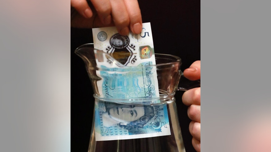 Bank of England Museum curator Jenni Adam dips the new five pound note into water at the Bank of England Museum in London, Tuesday, Sept. 6, 2016. A new gallery opening at the Bank of England Museum marks the launch of the new polymer fiver, which will go into circulation next Tuesday. (AP Photo/Frank Augstein)