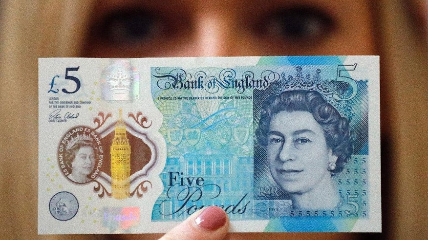 A Bank of England employee shows the new five pound note at the Bank of England Museum in London, Tuesday, Sept. 6, 2016. A new gallery opening at the Bank of England Museum marks the launch of the new polymer fiver, which will go into circulation next Tuesday. (AP Photo/Frank Augstein)