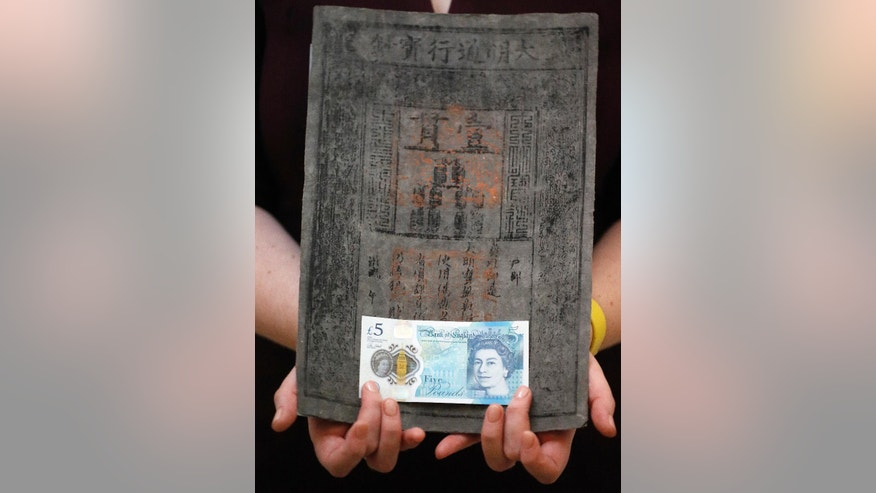 Bank of England Museum curator Jenni Adam holds the new five pound note in front of one of  the World's earliest of Ming dynasty paper money at the Bank of England Museum in London, Tuesday, Sept. 6, 2016. A new gallery opening at the Bank of England Museum marks the launch of the new polymer fiver, which will go into circulation next Tuesday. (AP Photo/Frank Augstein)