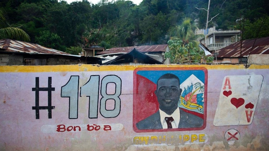 In this Aug. 25, 2016 photo, a mural feature senatorial candidate Guy Philippe in Pestel, Haiti. Philippe says he wants to bring prosperity to Haiti's mountainous southern peninsula, which features clear blue waters and lush forests but has scarce electricity, little infrastructure and widespread hunger. (AP Photo/Dieu Nalio Chery)