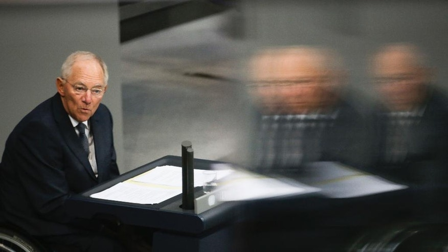 In this photo taken with reflection through windows at the visitors tribune, German Finance Minister Wolfgang Schaeuble delivers his speech during the first day of the budget 2017 debate at the German parliament Bundestag in Berlin, Tuesday, Sept. 6, 2016. (AP Photo/Markus Schreiber)