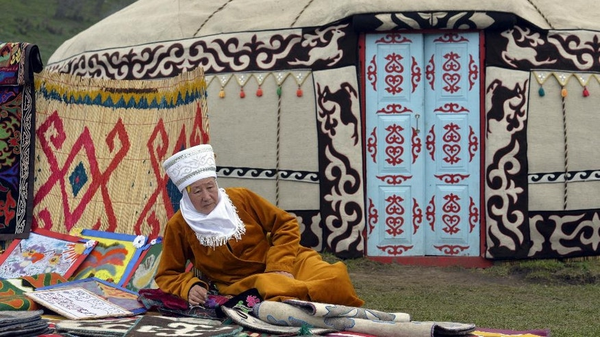 In this photo taken on photo taken on Sunday, Sept. 4, 2016, a Kyrgyz woman in traditional outfit displays traditional work rafts during the second World Nomad Games at Issyk Kul lake in Cholpon-Ata, Kyrgyzstan. The Games, which opened on Saturday on a picturesque mountain plain in eastern Kyrgyzstan, bring together athletes from 40 countries including Russia and the United States where nomadic traditions are strong. (AP Photo/Vladimir Voronin)