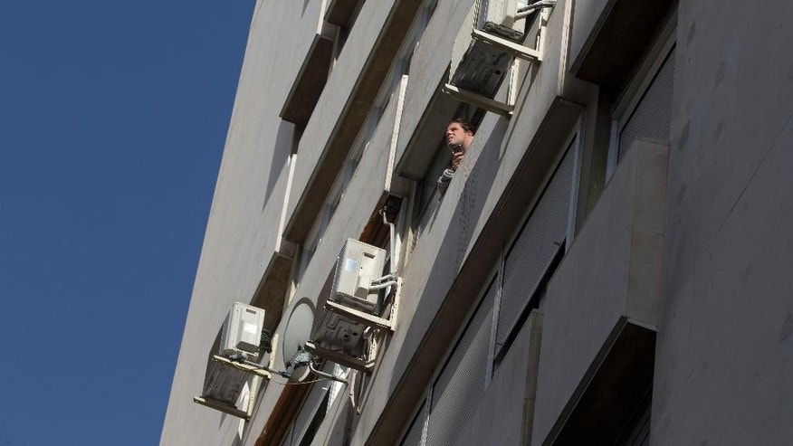 A man looks out of a window in a housing block with air conditioning units on the outside in Madrid, Spain, Tuesday, Sept. 6, 2016. Spain is currently suffering from a September heatwave with temperatures expected to raise to around 40 degrees centigrade (104 degrees Fahrenheit) Tuesday. (AP Photo/Paul White)