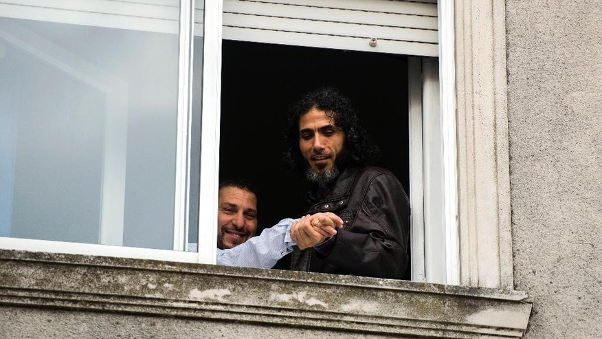 FILE - In this June 5, 2015, file photo, former Guantanamo detainee Abu Wa'el Dhiab from Syria, right, holds out the hand of fellow ex-prisoner Adel bin Muhammad El Ouerghi of Tunisia, showing off his wedding band in Montevideo, Uruguay. A friend said Monday, Sept. 5, 2016, that Dhiab is weak from a hunger strike and could need to be hospitalized. Dhiab is demanding that he be allowed to leave Uruguay. (AP Photo/Matilde Campodonico, File)