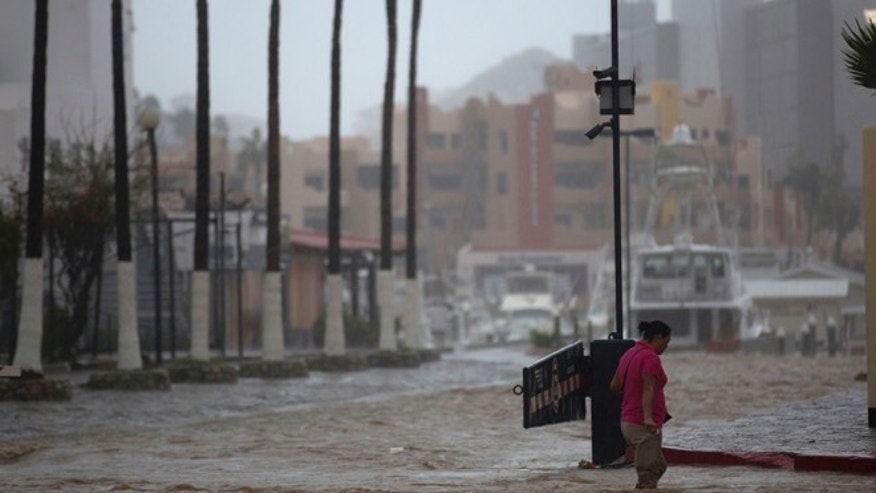 A woman wades through a street flooded by the heavy rains brought on by Hurricane Newton in Cabo San Lucas, Mexico, Tuesday, Sept. 6, 2016.