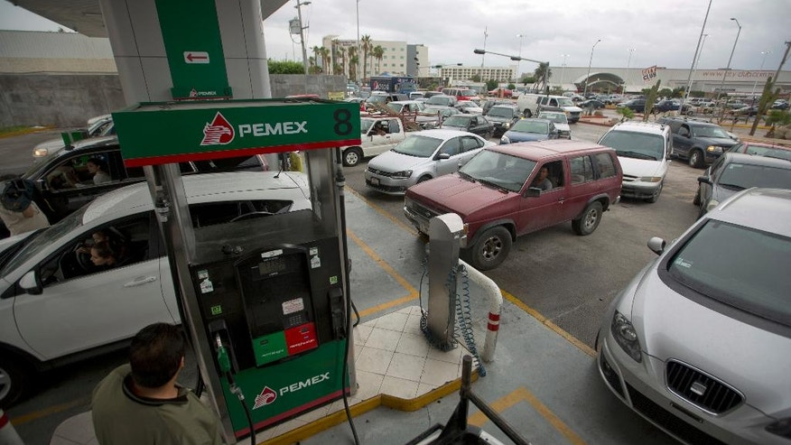 Drivers wait in line to fill up their gas tanks in preparation for the arrival of Hurricane Newton in Cabo San Lucas, Mexico, Monday Sept. 5, 2016. Authorities at the southern end of Mexico's Baja California peninsula ordered schools closed and set up emergency shelters as Hurricane Newton gained strength while bearing down on the twin resorts of Los Cabos for a predicted arrival Tuesday morning. (AP Photo/Eduardo Verdugo)