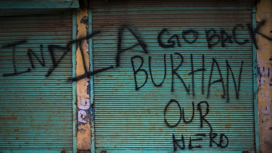 In this Aug. 31, 2016, photo, graffiti eulogizing militant commander Burhan Wani, who was killed in July, is painted on the shutters of shops in downtown Srinagar, Indian-controlled Kashmir. In death, Wani has become something that India has long feared: a homegrown militant openly lionized across the embattled region, a powerful symbol against Indian rule who has united Kashmir's many factions. Today, rock-throwing high school students paint his name on shuttered storefronts while everyone from fearsome insurgents to moderate politicians mourn him. (AP Photo/Dar Yasin)