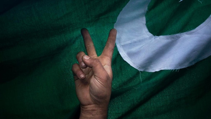 In this Aug. 29, 2016, photo, a Kashmiri protester flashes the victory sign standing beside a Pakistani flag during a protest in Srinagar, Indian controlled Kashmir. The current wave of protests began after the killing of militant commander Burhan Wani. In death, Wani has become something that India has long feared: a homegrown militant openly lionized across the embattled region, a powerful symbol against Indian rule who has united Kashmir's many factions. (AP Photo/Dar Yasin)