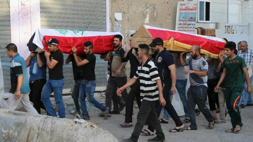 Mourners carry the Iraqi flag-draped coffins of bomb victims during their funeral procession in Baghdad, Iraq, Tuesday, Sept. 6, 2016. A car bombing in a bustling commercial area at Karradah neighborhood has killed and wounded civilians, late Monday, officials said. (AP Photo/Karim Kadim)