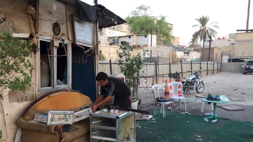 A man cleans the site of a car bomb in Baghdad, Iraq, Tuesday, Sept. 6, 2016. A car bombing in a bustling commercial area at Karradah neighborhood has killed and wounded civilians, late Monday, officials said. (AP Photo/Ali Abdul Hassan)