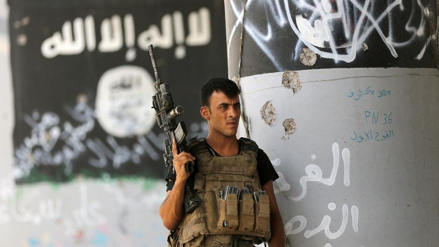 FILE -- In this June 27, 2016 file photo, a member of Iraqi counterterrorism forces stands guard near Islamic State group  militant graffiti in Fallujah, Iraq. Expelling the Islamic State group from the last territory it held along the Turkey-Syria border has dealt a critical blow to the extremists, cutting their supply lines. That could affect their ability to protect their last bastions the cities of Raqqa in Syria and Mosul in Iraq. (AP Photo/Hadi Mizban, File)