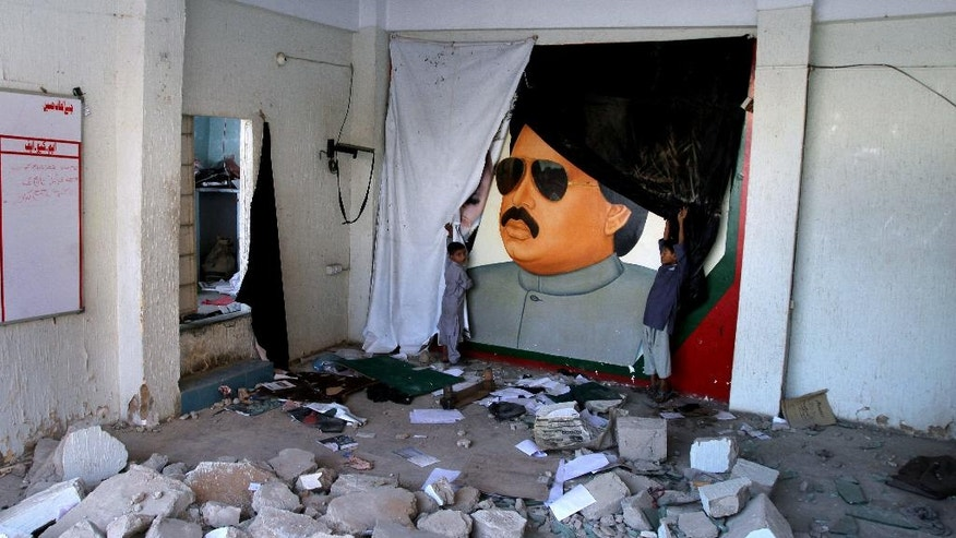 Pakistani children play next to the picture of Altaf Hussain, a top leader of Muttahida Qaumi Movement, or MQM, at one of his party offices demolished by authorities in Karachi Pakistan, Tuesday, Sept. 6, 2016. A government minister says authorities in Pakistan's largest city of Karachi have demolished over 100 offices of an ethnic party after its self-exiled leader Altaf Hussain made a speech against Pakistan. (AP Photo/Fareed Khan)