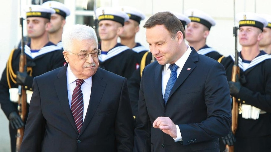 Polish President Andrzej Duda, right, and Palestinian President Mahmoud Abbas share a word after inspecting the honor guard during an official welcoming ceremony in the courtyard of the presidential palace in Warsaw, Poland, Tuesday, Sept. 6, 2016. (AP Photo/Czarek Sokolowski)